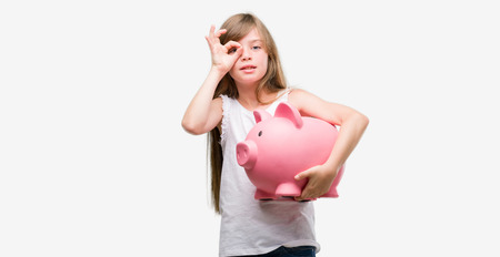 Young blonde toddler holding piggy bank with happy face smiling doing ok sign with hand on eye looking through fingers