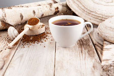 Photo for Mug of chaga tea on wooden table in a rustic style. Nearby are lied natural Chaga birch mushrooms. Healthy beverage is used in alternative medicine. - Royalty Free Image