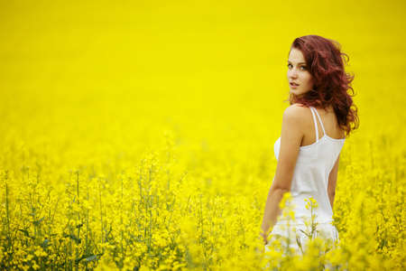 young beautiful girl in yellow field