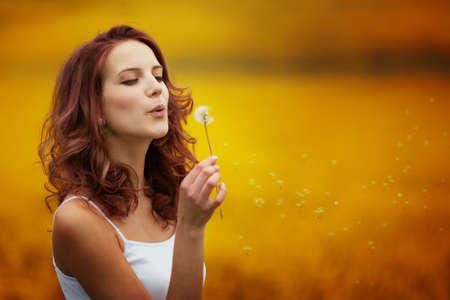 happy beautiful woman blowing dandelion in the field