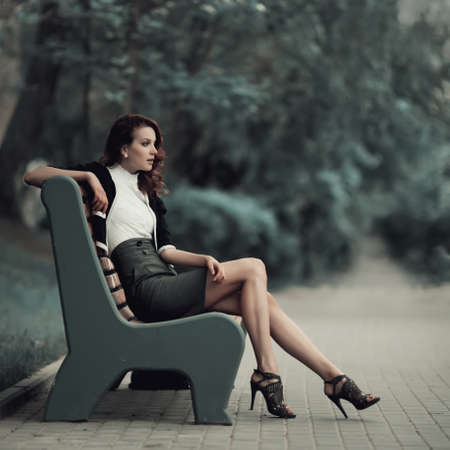 young beautiful girl sitting on bench in parkの写真素材