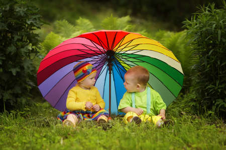 cute little children under colorful umbrellaの写真素材