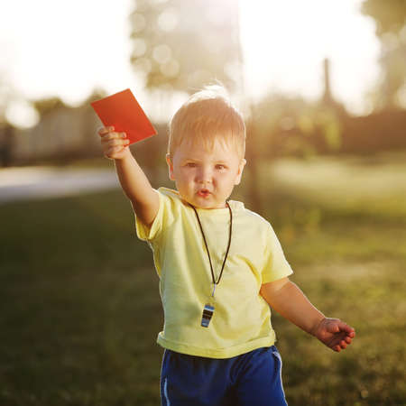photo of cute little referee with red card