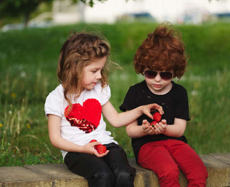 funny boy and girl sharing strawberry