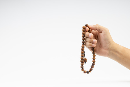 Photo for Hand holding a muslim rosary beads or Tasbih on white background. Copy space and selective focus - Royalty Free Image