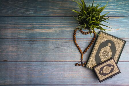 Foto de Flat lay view of vase, tasbih or rosary beads and Holy book of Quran with arabic calligraphy meaning of Al Quran over wooden paper background. Selective focus and crop fragment - Imagen libre de derechos