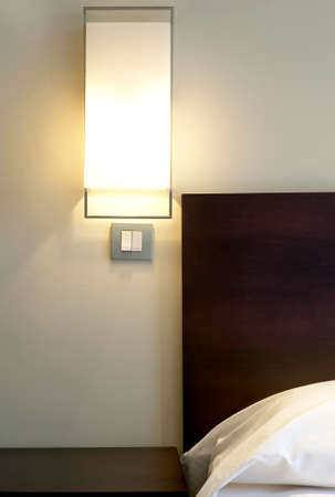 Hotel room detail with lamp and bed  Vertical