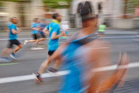 Foto de Marathon runner in motion on the street. Healthy lifestyle. Exercise - Imagen libre de derechos