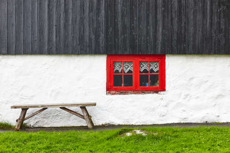 Traditional picturesque faroe islands house black wooden roof red window