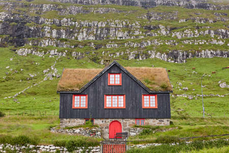 Traditional picturesque faroe islands black wooden house with green roof