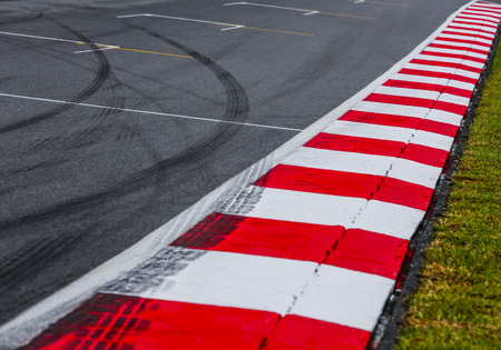 Photo for Asphalt red and white kerb of a race track detail with tire marks. Motorsports racing circuit close up.  - Royalty Free Image