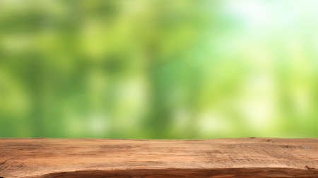 Foto de Emtpy wooden table with blurry nature background and flares, space for your text or product - Imagen libre de derechos