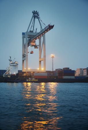 Crane loading containers in a cargo ship at night.