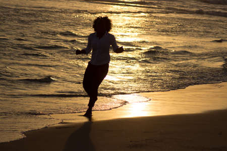 A woman runs the evening at the beach. She its doing sport to keep fit