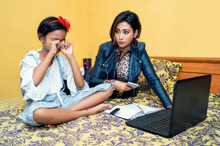 Photo pour daughter getting scolded by her mother, studying online at home - image libre de droit