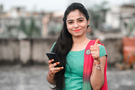 Photo pour Pretty young Indian woman using her phone and showing thumbs up sign. - image libre de droit