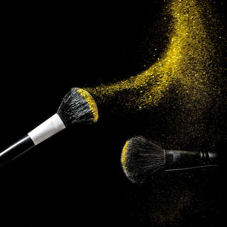 Photo for Make-up brush with gold powder explosion on black background. - Royalty Free Image