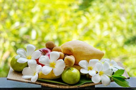 Photo pour Tropical fruits decorated with frangipani flowers. - image libre de droit