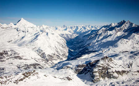 Photo pour Perfect view of the Mattertal and surrounding mountains like weisshorn in Zermatt sunset view, with blue sky and perfect light. The snowy Swiss mountains and landscape in winter is extraordinary. After a long skiing day these views are incredible. - image libre de droit