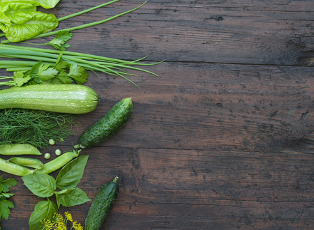 Photo for Green vegetables on wooden background (peas, parsley, basil, cucumber, dill, onion ,salad) - Royalty Free Image