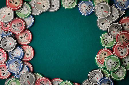 Poker chips on green felt casino table background.