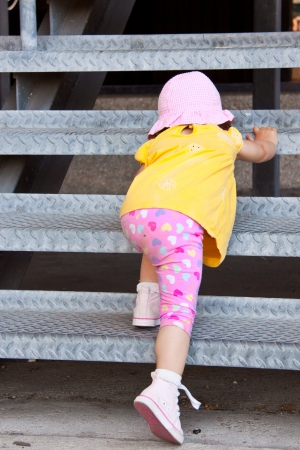 Little girl trying to escalate some metal stairs