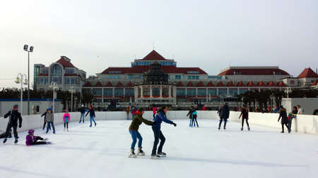 Sopot, Poland - February 10, 2019: Children and adults are skating on an artificial ice rink at the pier in Sopot, Poland.