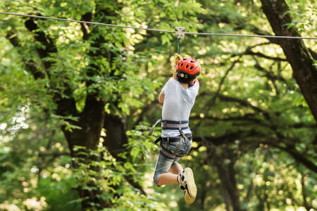 Photo for Little boy overcomes the obstacle in the rope park. Climbing in high rope course enjoying the adventure. Adventure climbing high wire forest - people on course in mountain helmet and safety equipment - Royalty Free Image
