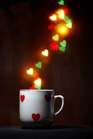 Mug emits steam of glowing hearts on dark background with copy space