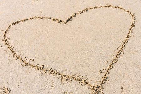 Photo pour Heart shape drawn on sandy beach. Concept of love, romantic relationship - image libre de droit