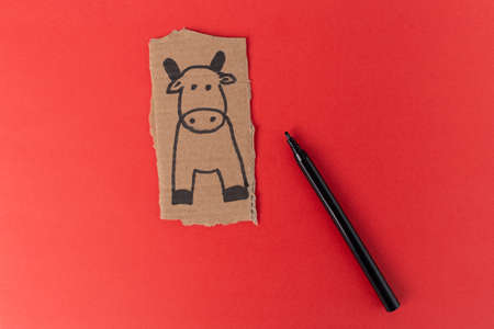 craft cow made of cardboard, How to make bull or ox at home. Children art project. DIY concept. making toy on red. Step by step photo instruction. Step 1