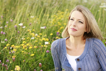 Happy middle aged woman in wild flower fieldの写真素材