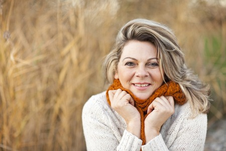 Photo pour Happy middle aged woman with pullover and scarf outdoor - image libre de droit