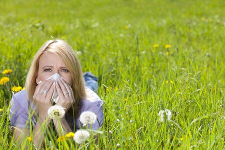 Mature woman with hayfever and handkerchief lying in the meadow