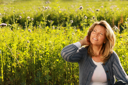 Foto de Middle age woman in her leisure time with hand in her hair sitting in front of a flowerfield - Imagen libre de derechos