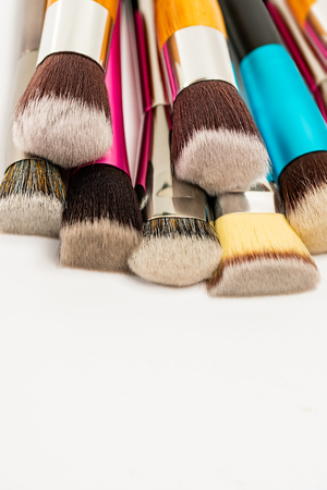 Photo pour Colorful Collection of Makeup Foundation Brushes on White Background. Various Soft Bristle Cosmetic Foundation Brush. Close Up. Selective Focus. - image libre de droit