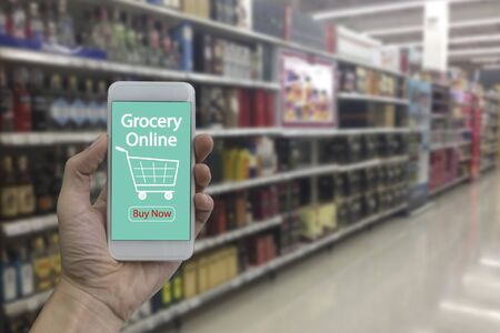 Hand use smartphone with grocery online on screen over blurred supermarket and retail store in shopping mall interior background.