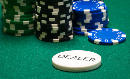 Dealer chip, and other varied poker chips, on green felt.