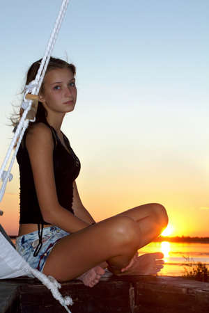 Beautiful teen girl sitting at stern of the ship