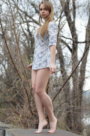 Barefooted pretty blonde wearing white shirt posing like a statue