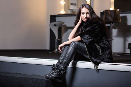 Pretty young woman wearing fur coat and leather pants posing in studio