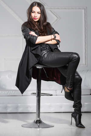 Foto de Young thoughtful lady posing in studio sitting on a chair and dressed in black clothes. - Imagen libre de derechos