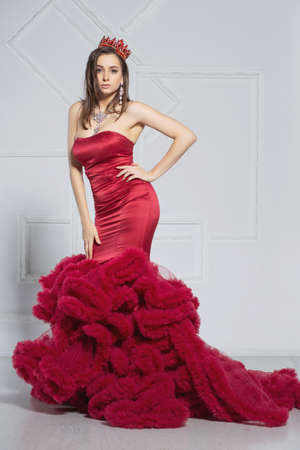 Photo pour Lovely young lady posing in a studio dressed in an elegant red dress and a crown - image libre de droit
