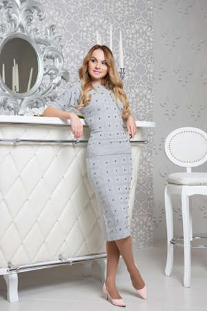 Photo pour Beautiful woman posing in studio dressed in a gray dress and shoes - image libre de droit
