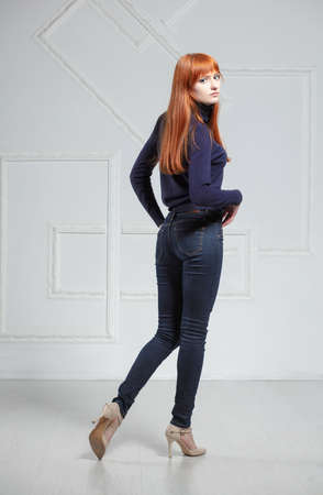 Photo pour Attractive redhead woman posing in studio wearing a sweater and jeans - image libre de droit