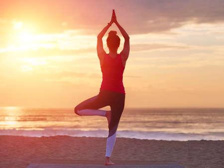 Photo pour Beautiful practicing yoga on beach. Sea and sunset sky background. Yoga concept. - image libre de droit