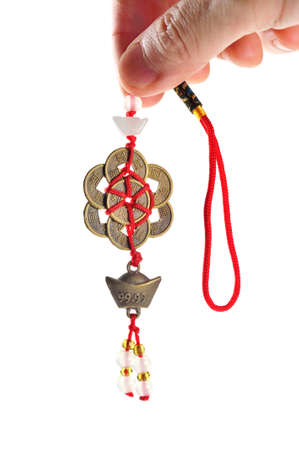 Hand held ancient Chinese coins connected by red strings and knots and decorated with small jades