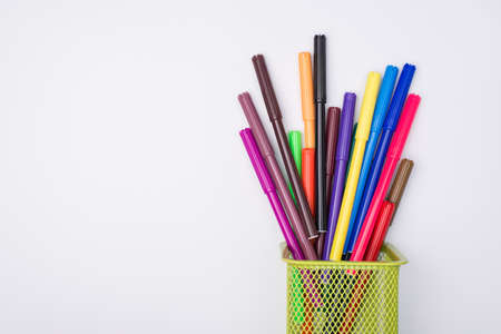 Photo pour Drawing supplies concept. Top above overhead view flat-lay photo of colorful markers in pencil cup isolated on white background - image libre de droit