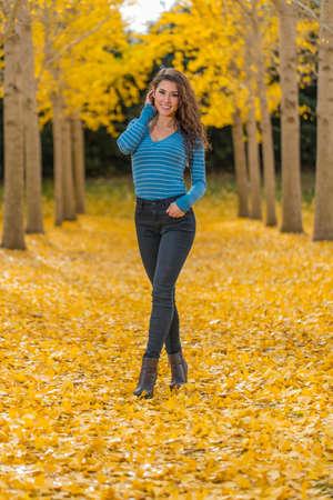 Photo pour A beautiful brunette model with yellow fall foliage - image libre de droit