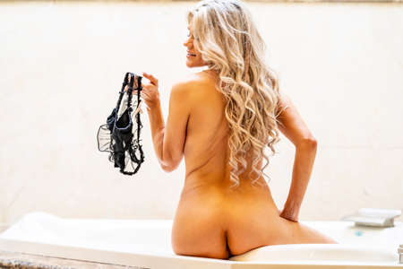 Photo for A gorgeous blonde model poses while taking a bath - Royalty Free Image